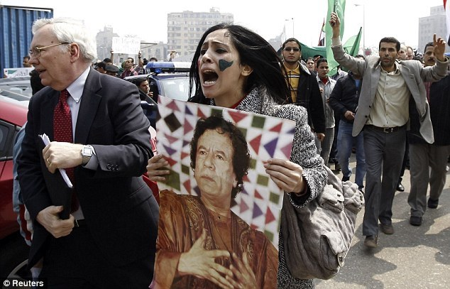 A Libyan woman holds up a picture of Muammar Gaddafi, 2011